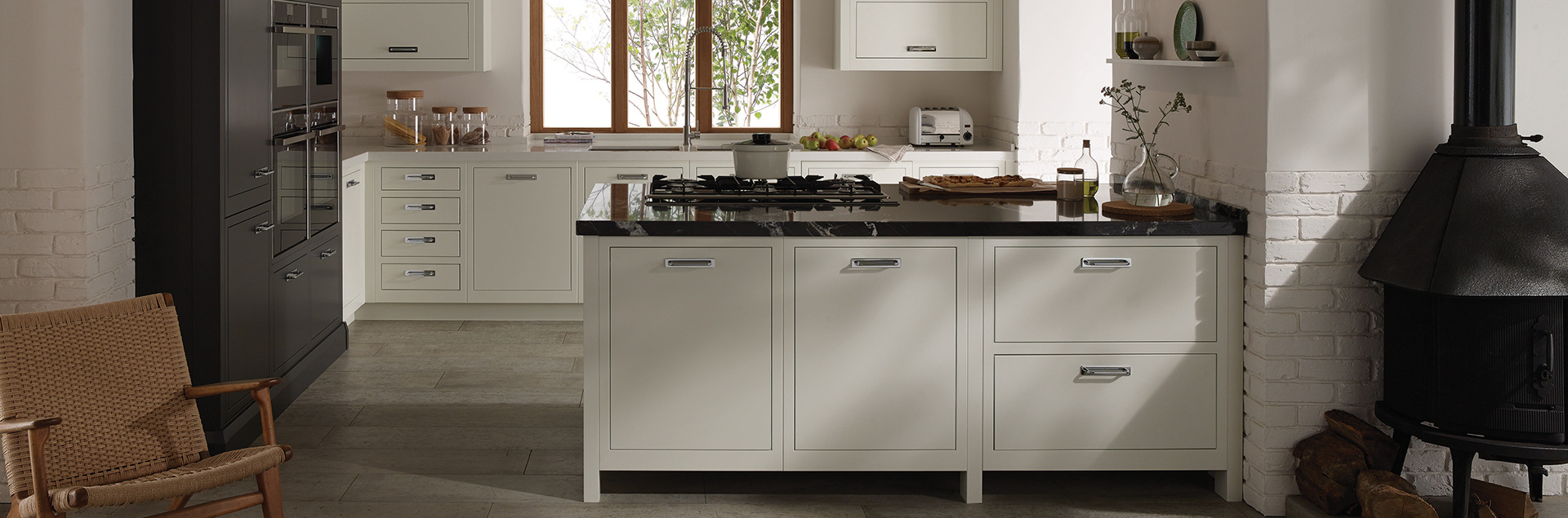 A slab inframe kitchen painted in two tones. The main sections of the kitchen are painted in a porcelain finish with the tall housing cabinets finished in a graphite paint colour. The surfaces are also a mix of natural marble and quartz.