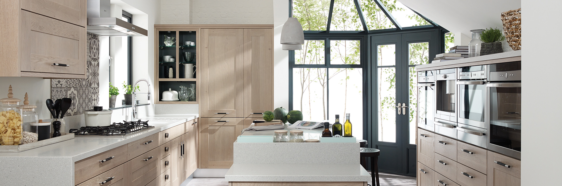 A large contemporary style kitchen, with solid oak shaker doors. Silestone surfaces, builtin Neff appliances, a large flexible spray tap and an island unit with space for dining.